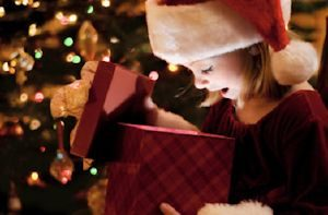 lITTLE GIRL LOOKING INSIDE A WRAPPED PRESENT